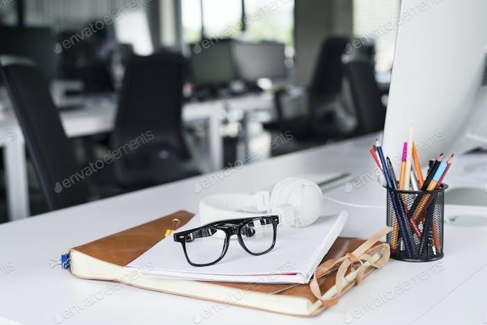 Офисный стол с компьютером, ноутбуком и очками.