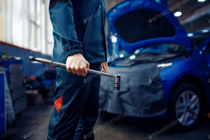 Worker in uniform holds wrench, car service