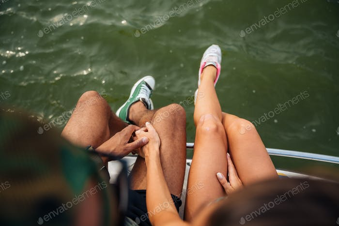 Legs of young couple in sneakers sitting near the sea