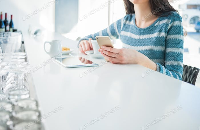 Mujer en el café Uso un teléfono Móvil