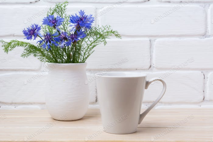 White coffee latte mug mockup with cornflower in rustic vase