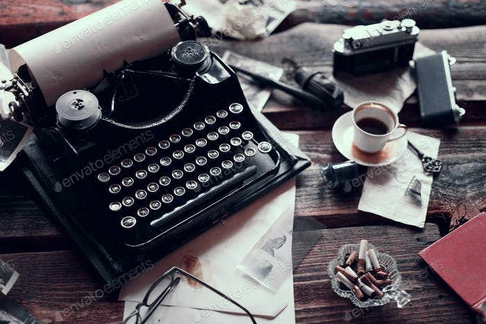 Retro typewriter on a wooden table with different vintage things