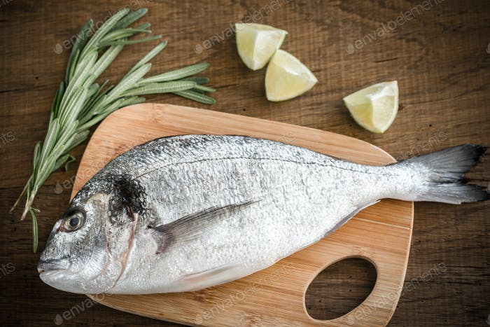 Fresh dorada with ingredients on the wooden board