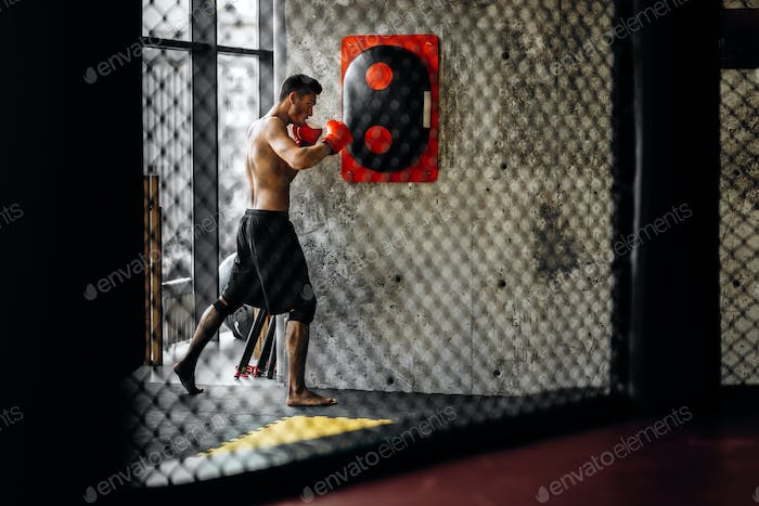 Sportsman with a naked torso and in the red boxing gloves hits equipment for boxing on a concrete