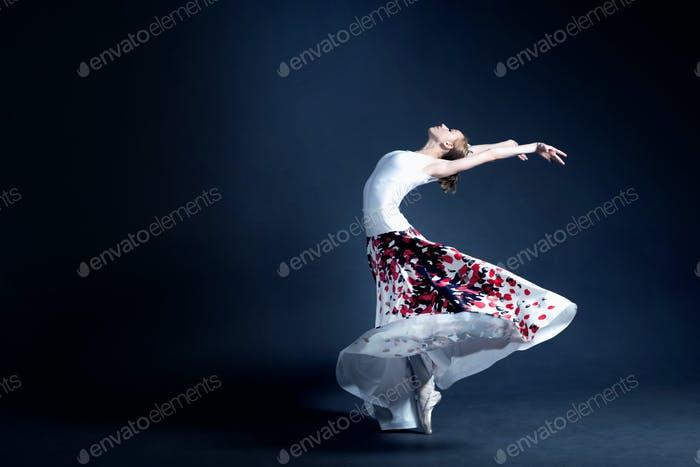 Young ballerina is dancing in a dark photostudio