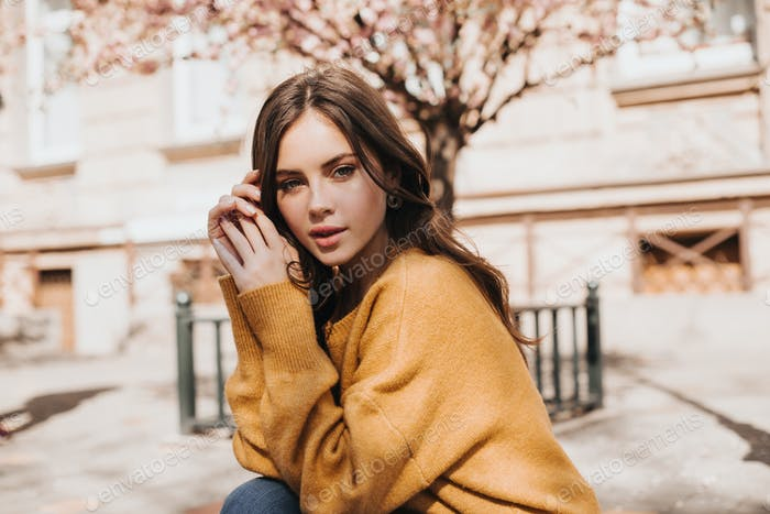 Lady in yellow sweater looks into camera against the background of sakura. Green eyed woman resting