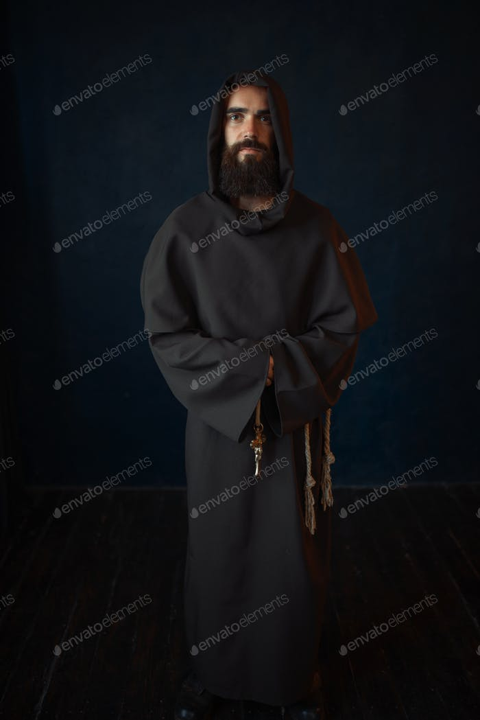 Monk in black robe with hood, religion