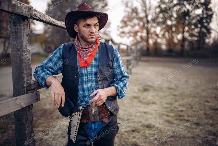 Brutal cowboy with cigar in the horse corral
