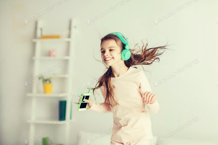 girl jumping on bed with smartphone and headphones