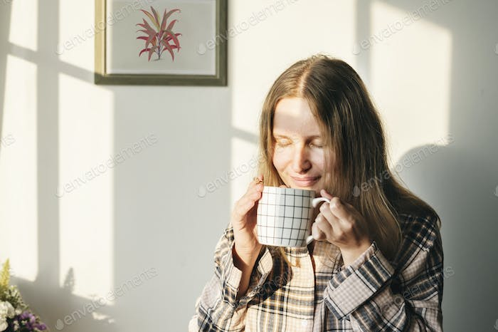 Caucasian woman drinks coffee in the morning