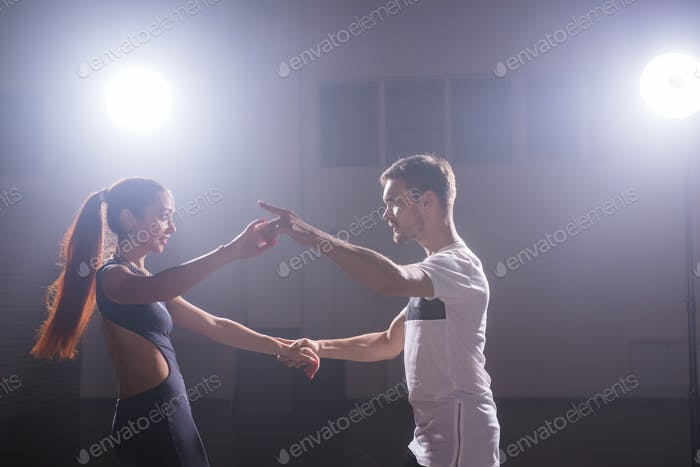 Young couple dancing social danse kizomba or bachata or semba or taraxia in dancing class background