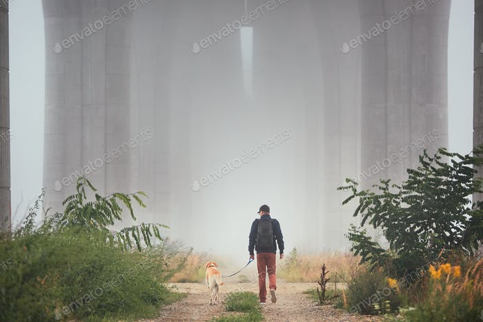 Man with dog in mysterious fog
