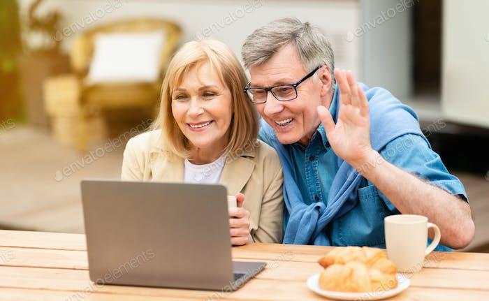 Friendly mature couple chatting online via laptop near RV at campsite