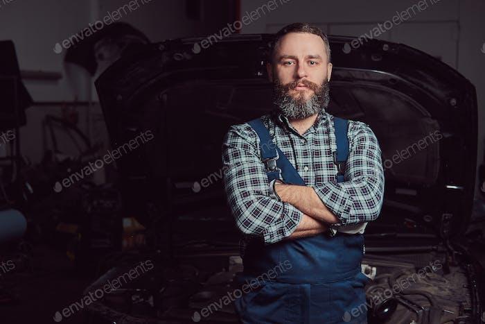 Bearded expert mechanic dressed in a uniform