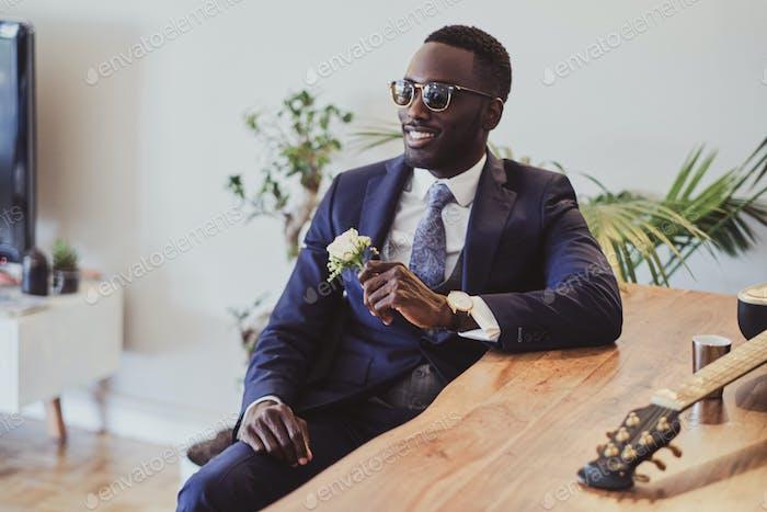 Porträt des eleganten Mannes sitzt neben dem Tisch