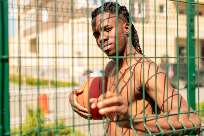 Young African basketballer holding ball while looking through fence bars