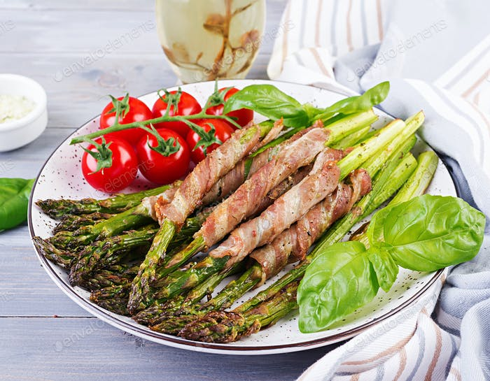 Grilled green asparagus wrapped with bacon on wooden table.