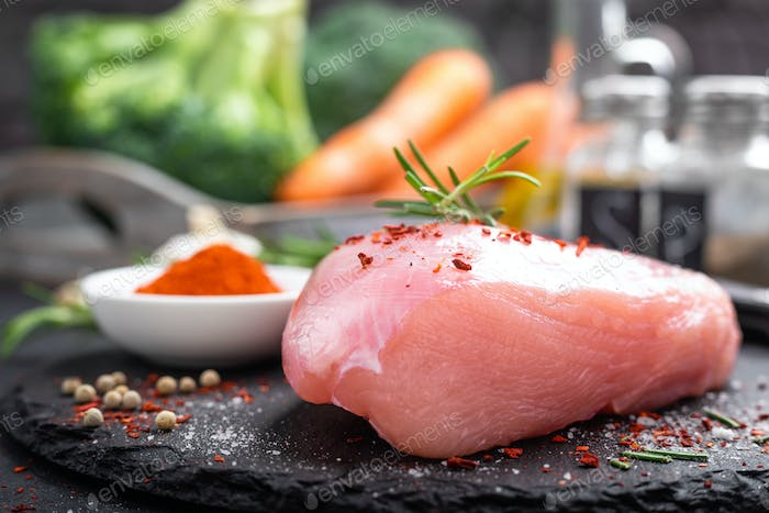 Fresh raw turkey meat fillet with ingredients for cooking
