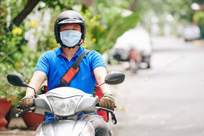 Courier riding on scooter
