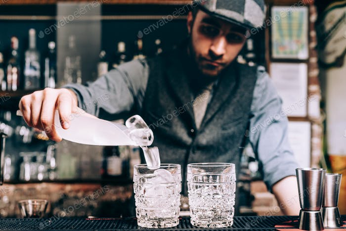 barman preparing cocktails, pouring ice and wiskey in fresh alcoholic beverages