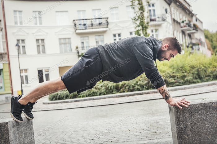 Athletic man training on a street.