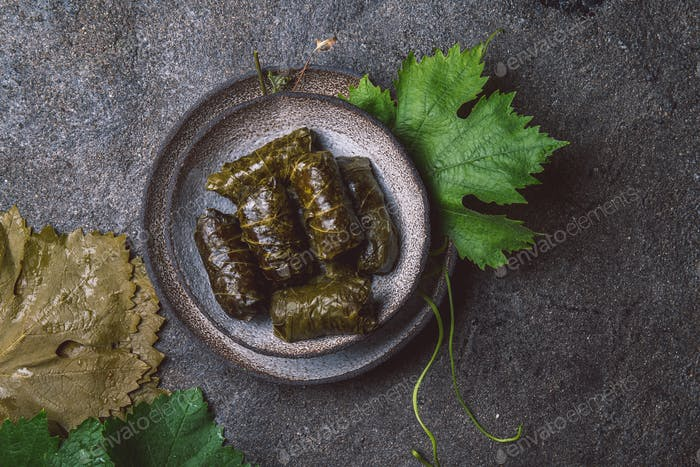 Mexican Chilean cuisine. Ninos envueltos. Grape leaves stuffed wish meat on clay plate