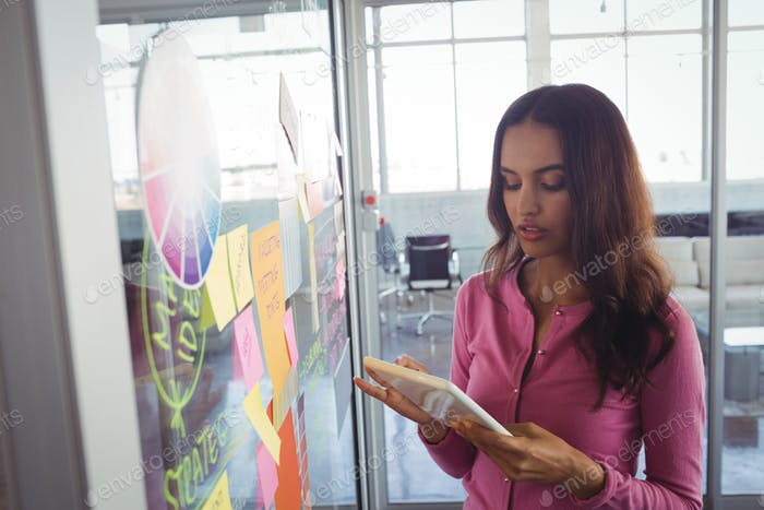 Female designer holding digital tablet by adhesive notes on glass in office