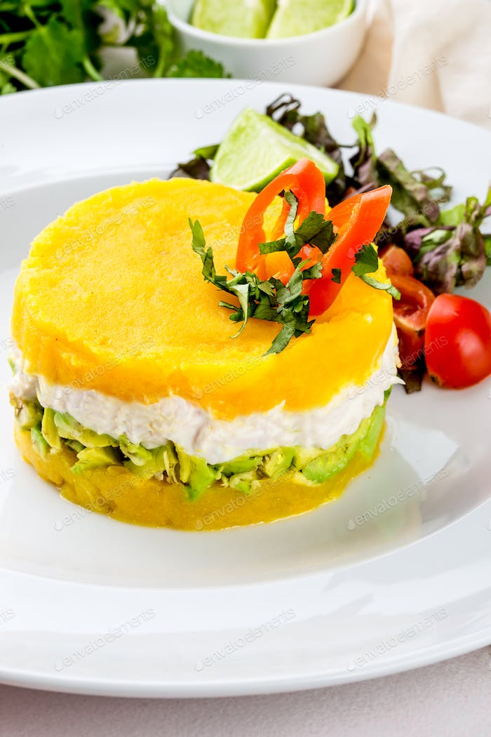 Traditional peruvian dish Cause from yellow potato, chicken, avocado on white plate.