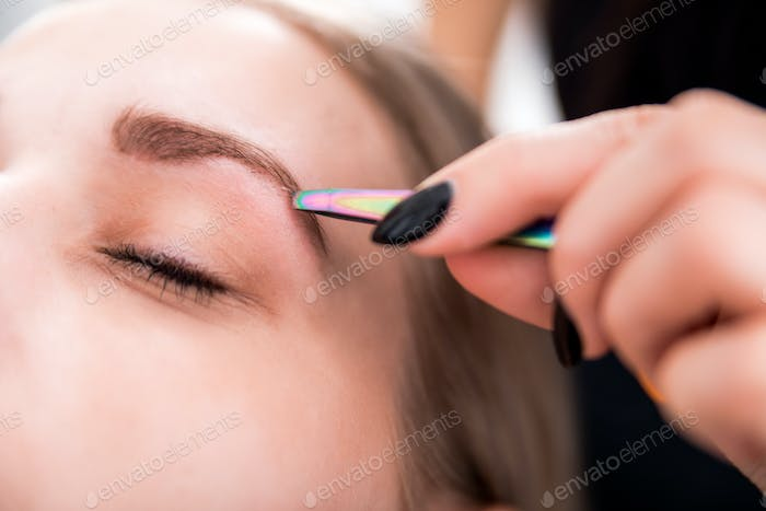 Plucking eyebrows with tweezer by beautician at beauty salon