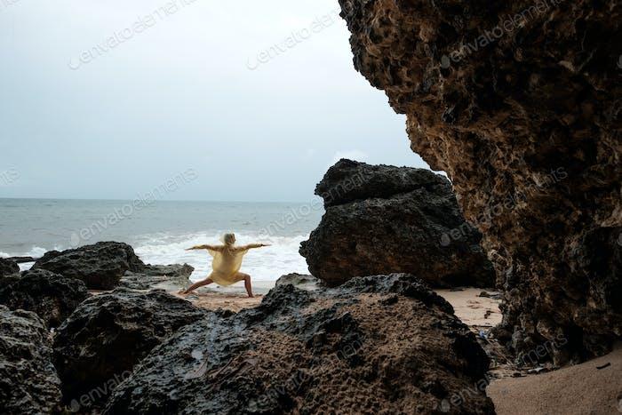 Frau im Regenmantel tun Balance Yoga Asana am Meer Strand während des Sturms.