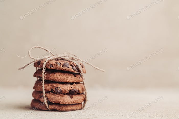 Stacked chocolate chip cookies on grey table