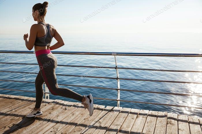 Rückansicht der weiblichen Sportlerin Workout an der Strandpromenade, Joggen in der Nähe des Meeres