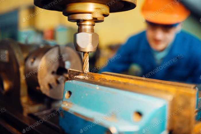 Male worker works on lathe closeup view, plant