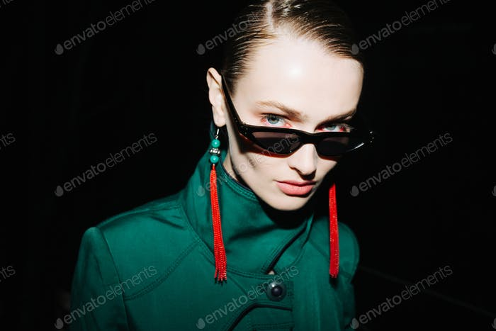 Young woman in fashionable sunglasses and red earrings confidently looking in camera at night