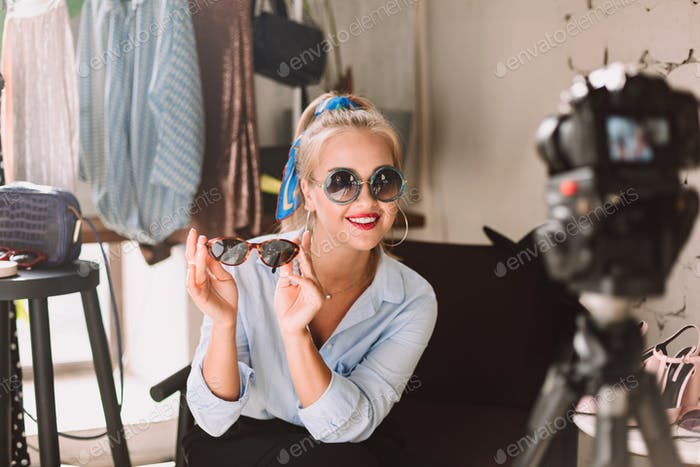 Beautiful smiling fashion blogger in sunglasses happily looking