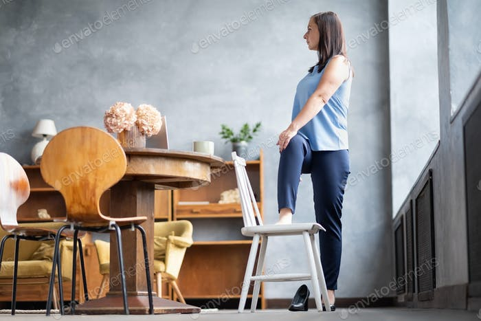 Female office worker stand in yoga pose twisting spine using chair.