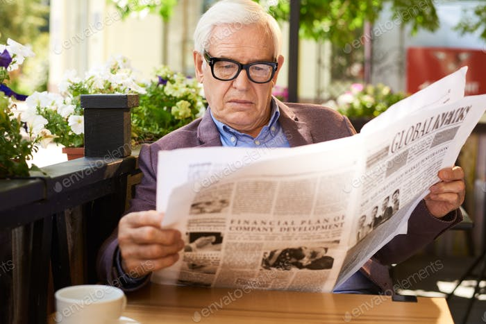 Senior Man Reading Newspaper oat Table in Cafe