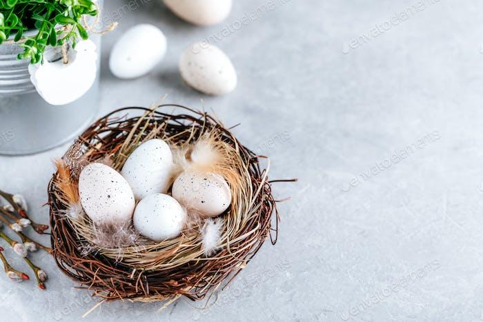 Ostereier im Nest auf grauem Steinhintergrund, Kopierraum.