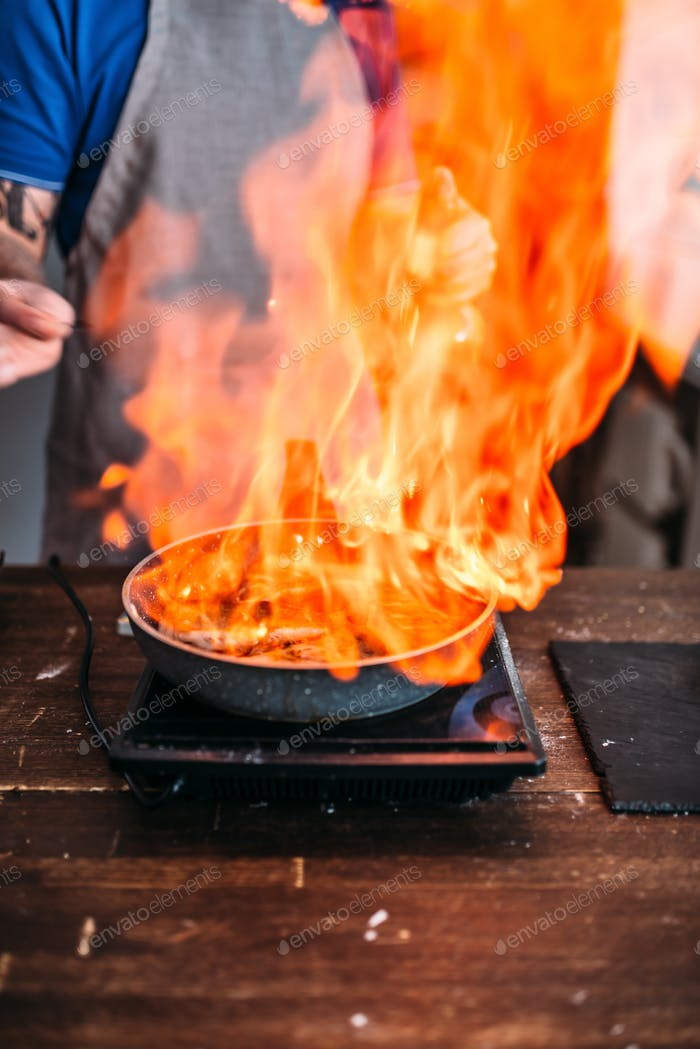Male person against frying pan with fire