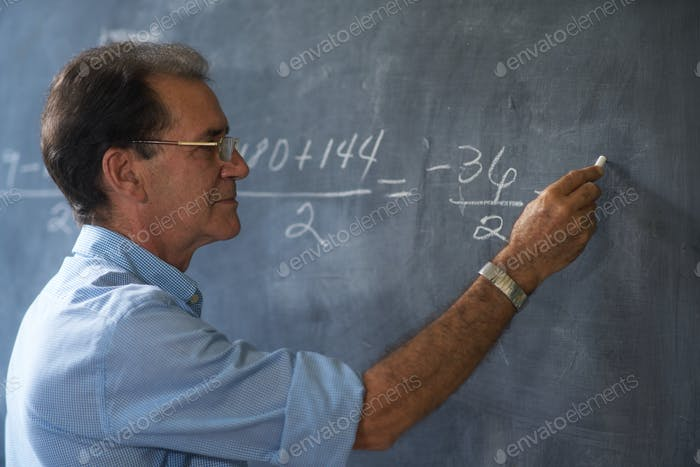 Teacher Writing Math Formulas On Blackboard At High School