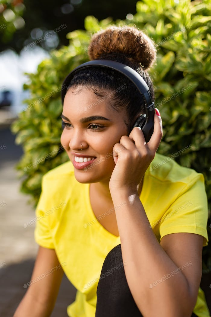 Pretty young black african american woman listening to music wit