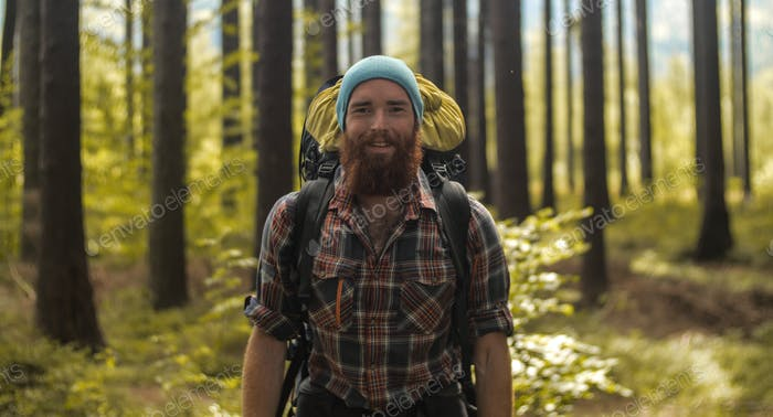 portrait of a caucasian male hiker standing  outdoors in a forest with a backpack