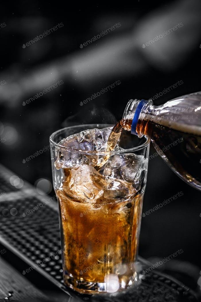 Cola in das Glas gießen