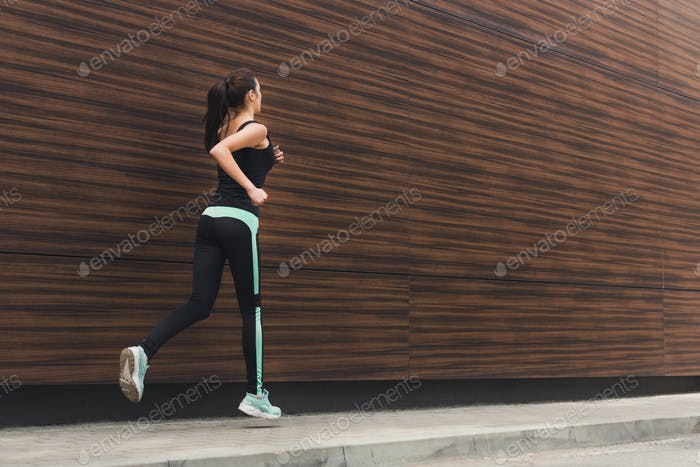 Young woman running in city copy space