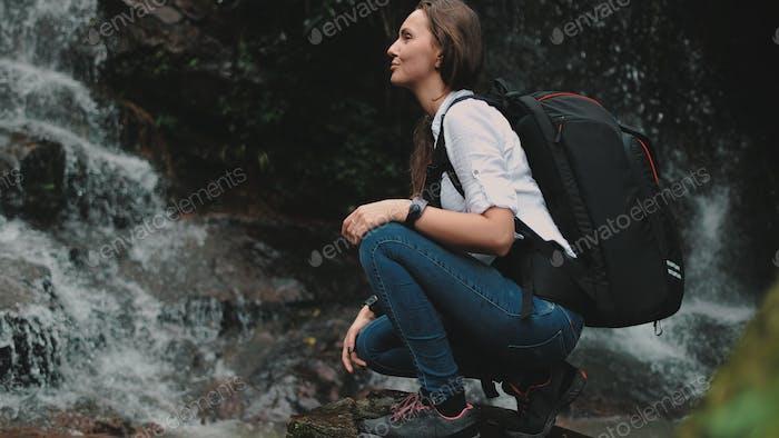 woman traveler crouch near splashing waterfall