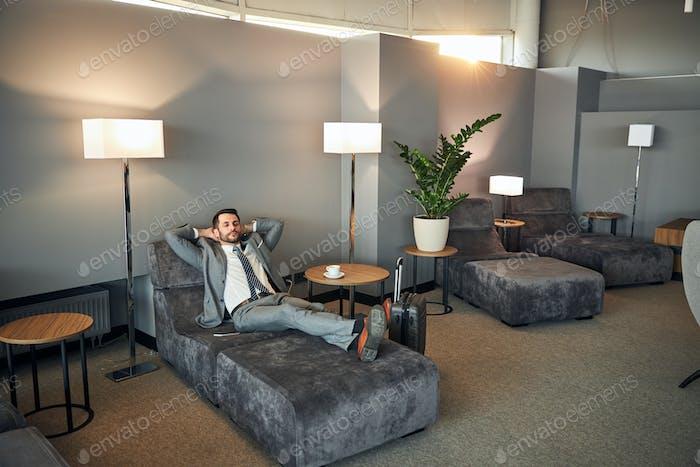 Hombre durmiendo en una habitación de aeropuerto para descansar