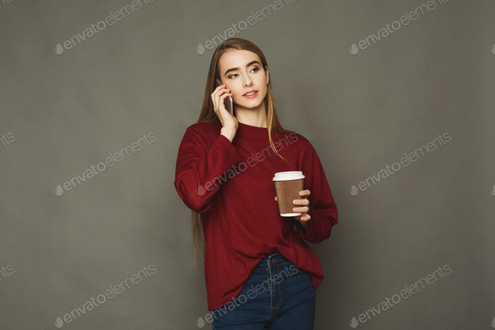 Woman speaking on phone and having coffee