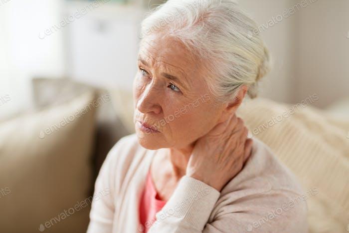 ältere Frau leidet an Nackenschmerzen zu Hause