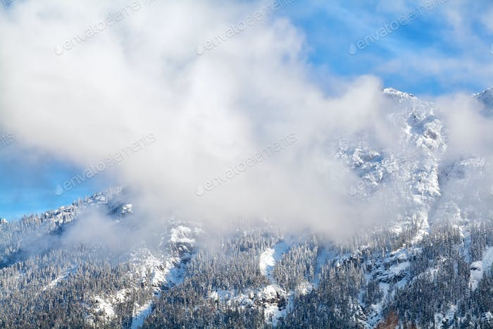 clouds over alpine winter peaks
