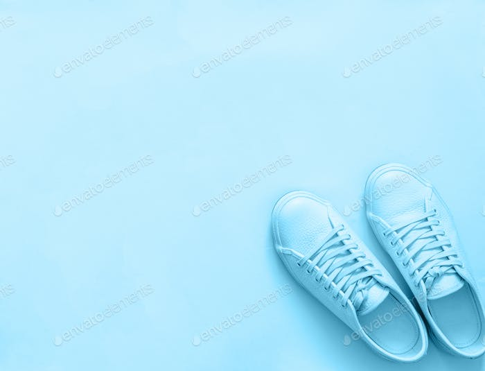 Blue sneakers on blue background, copy space